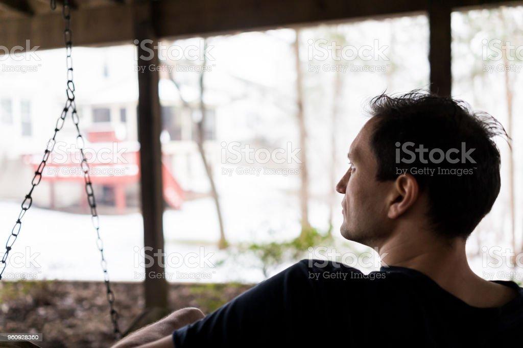 Schommel In Huis : Closeup van jonge man zit op de schommel onder houten dek van huis