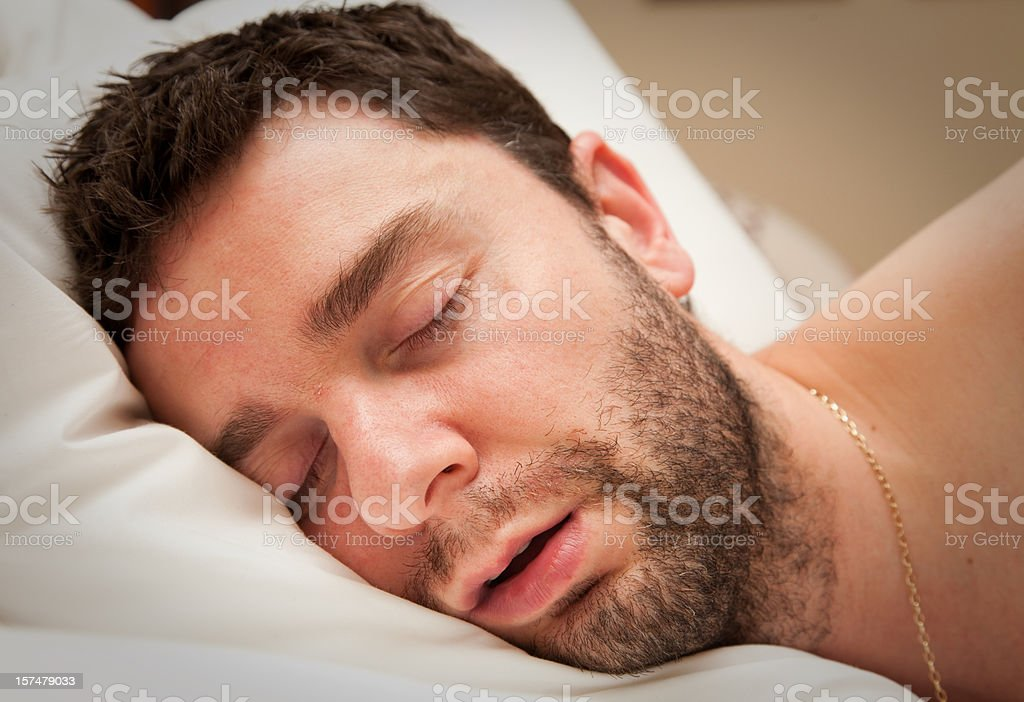 Close-up of young man with beard in sound sleep in bed royalty-free stock photo