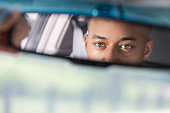 In this closeup, there is a rear view mirror at the top of the photo with a reflection of a young African American male's partial face.  He is sitting in a car looking in the mirror.  At the bottom of the photo, there is copy space.