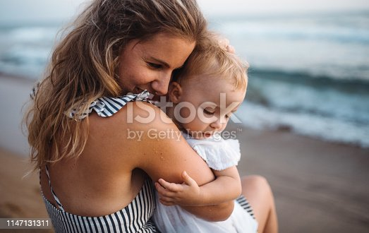 A close-up of young mother with a toddler girl on beach on summer holiday.