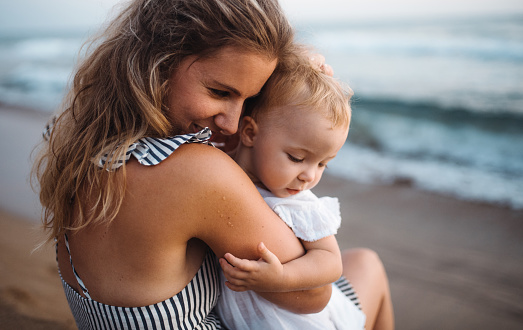 Close-up of young mother with a toddler girl on beach on summer holiday.