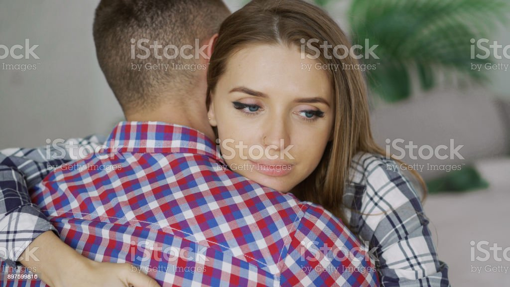 Closeup of young upset couple embrace each other after quarrel. Woman looking wistful and sad hug her boyfrined at home stock photo