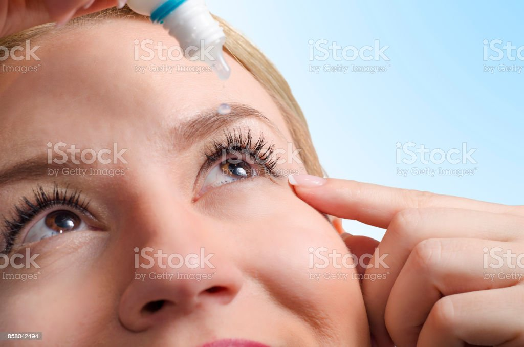 Closeup of young woman applying eye drops stock photo