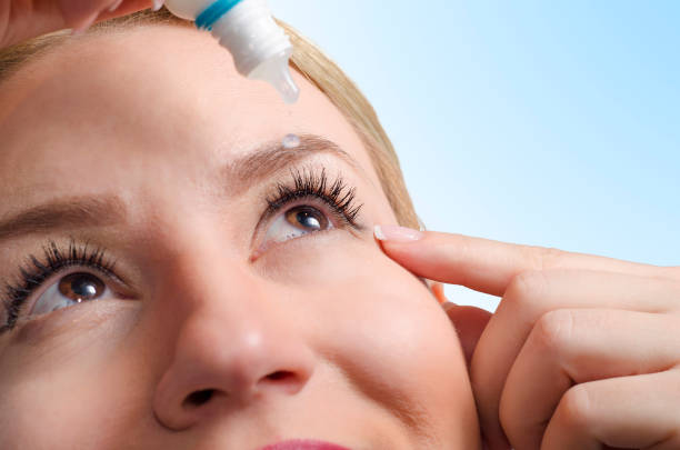closeup of young woman applying eye drops - dry stock photos and pictures
