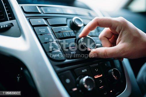istock Closeup of young woman hand control radio volume 1189839322
