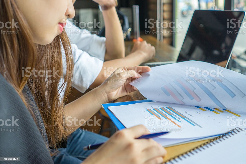 Close-up of young woman hand turning page of chart document stock photo