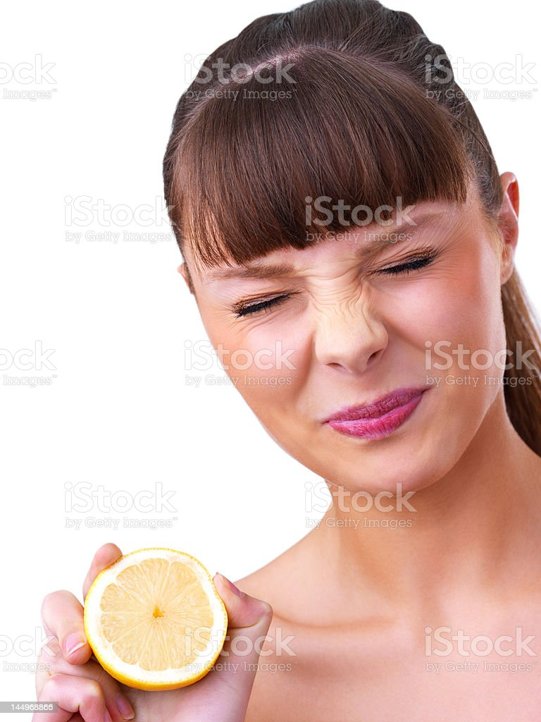 Close-up of Young woman holding half cut sour lemon royalty-free stock photo