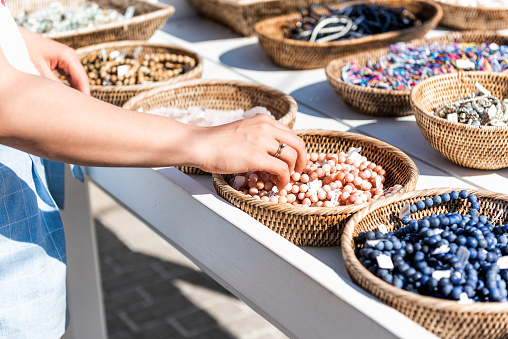 Closeup of young woman shopping for colorful stone beach bracelets touching hand in outdoor market shop store in European, Greece, Italy, Mediterranean town, village in summer