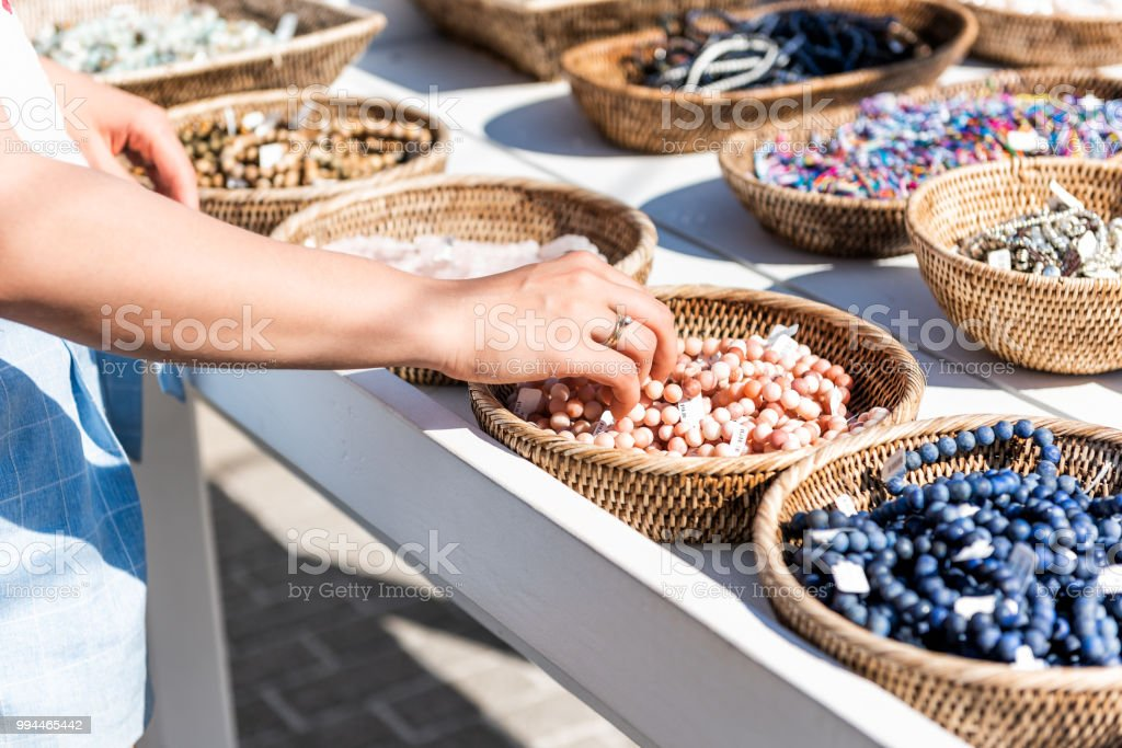 Closeup of young woman shopping for colorful stone beach bracelets touching hand in outdoor market shop store in European, Greece, Italy, Mediterranean town, village in summer stock photo