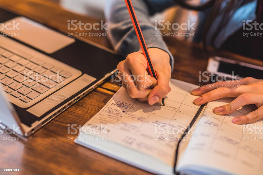Close-up of young woman taking notes. stock photo