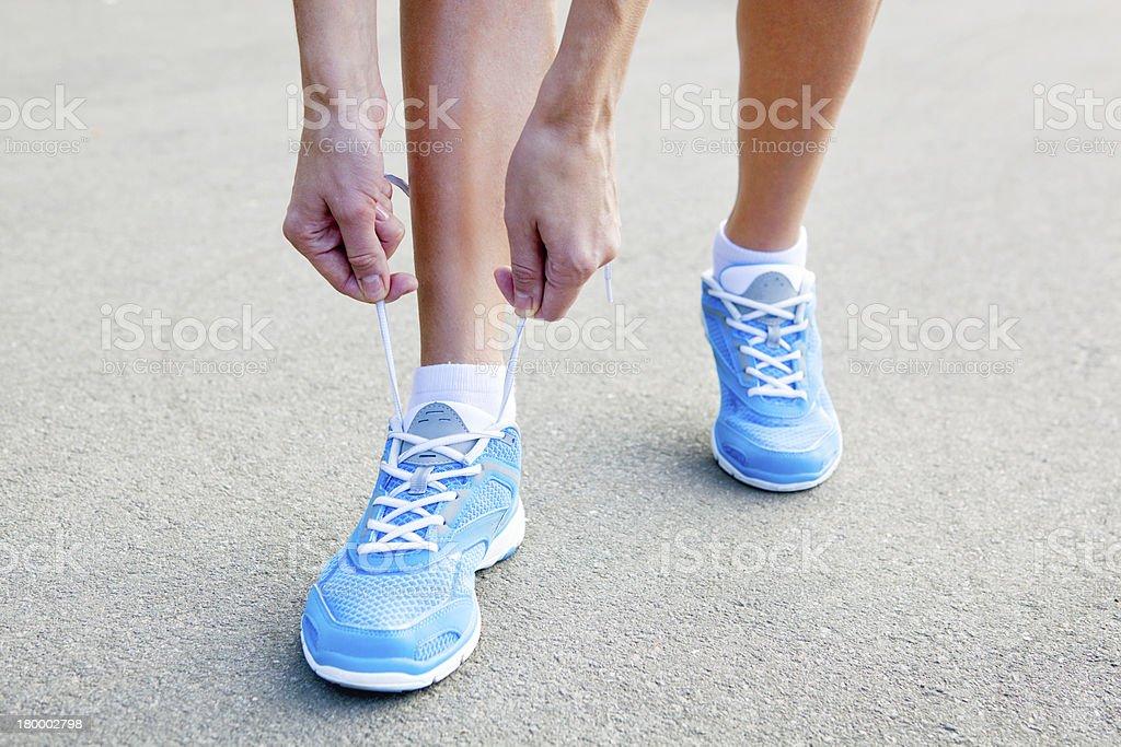 젊은 여자 클로즈업 끼워팔기 스포츠 신발. royalty-free 스톡 사진