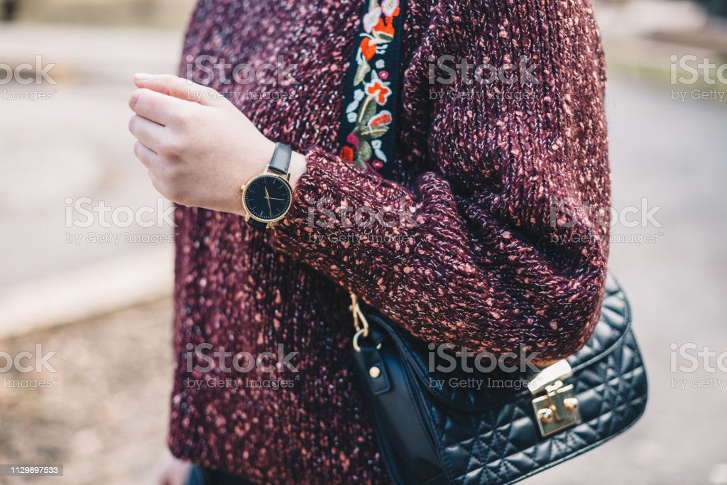 Close-up of young woman\'s torso in red sweater, wearing hand watch...