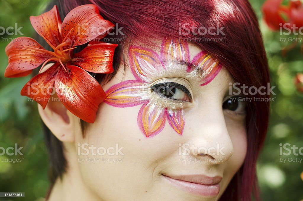 Closeup of young woman with lily face paint. royalty-free stock photo