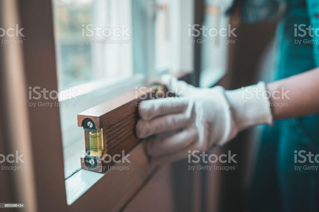Close-up of young woman with working tools renovating home stock photo