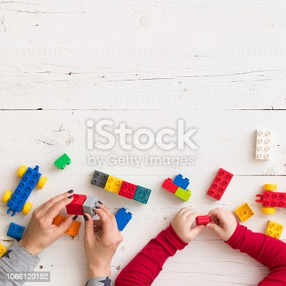 istock Closeup of young woman's and child's hands playing with toys and plastic bricks on white wooden table background 1066120152