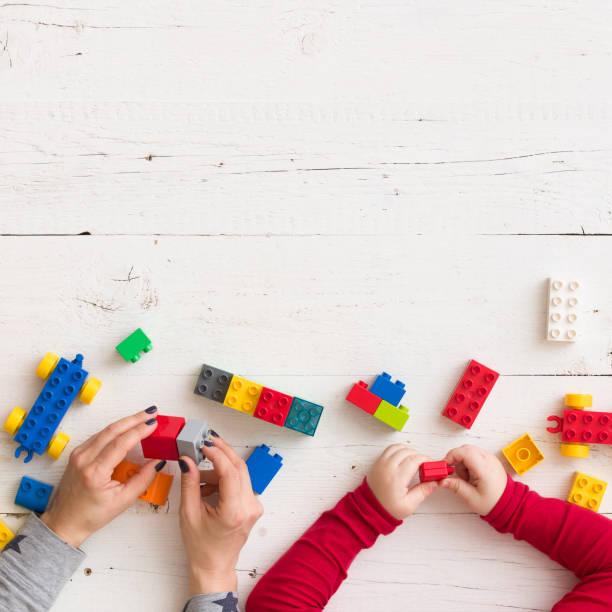 nahaufnahme der jungen frau und des kindes hände spielen mit spielzeug und plastikziegelsteine auf weißer holztisch hintergrund - wachstumstabelle baby stock-fotos und bilder