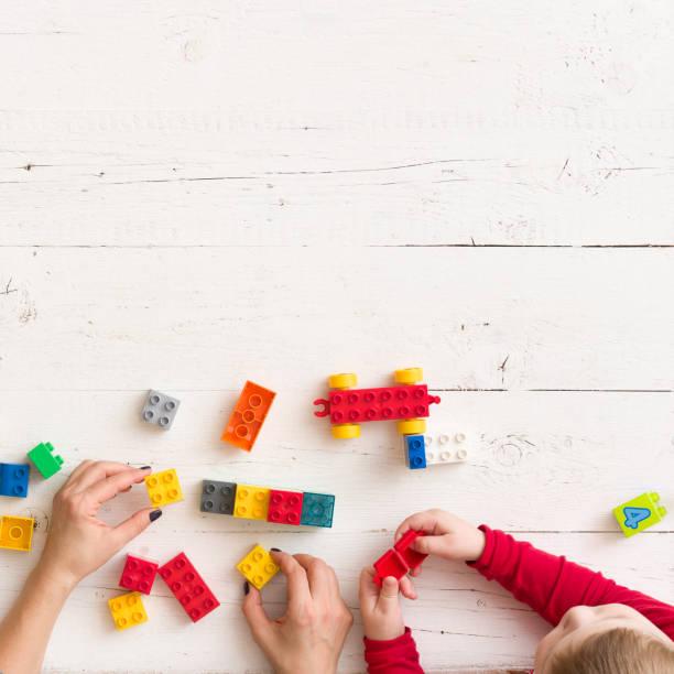 nahaufnahme der hände junger frauen und kinder, die mit spielzeug und plastiksteinen auf weißem holztisch spielen - wachstumstabelle baby stock-fotos und bilder