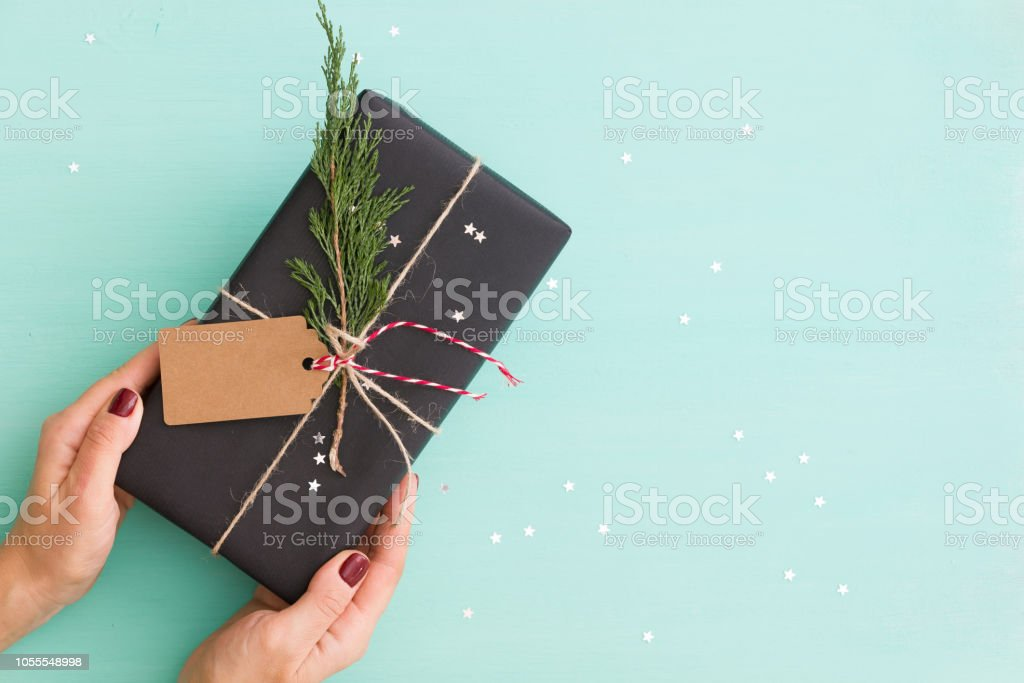 Closeup Of Young Womans Hands Holding Christmas Or Birthdays Gift Wrapped In Black Paper Present