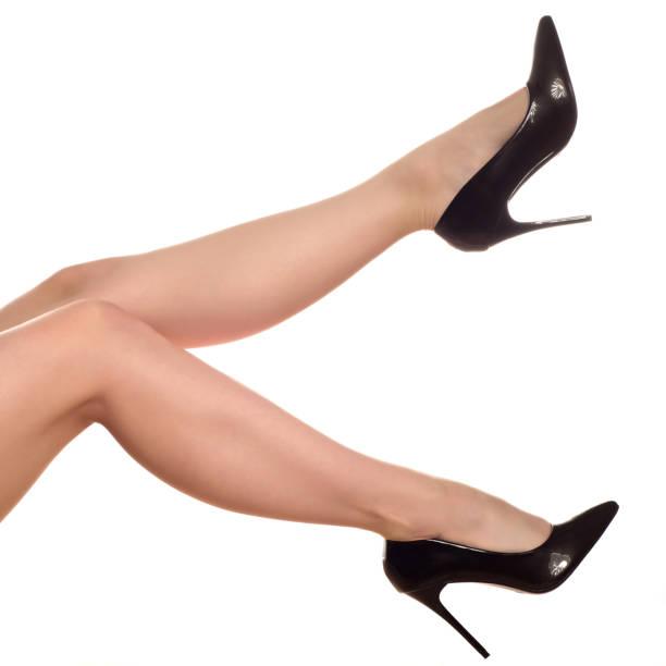 nahaufnahme der jungen frau beine in hochhackigen schwarzen schuhen isoliert auf weiss - schwarze hohe schuhe stock-fotos und bilder