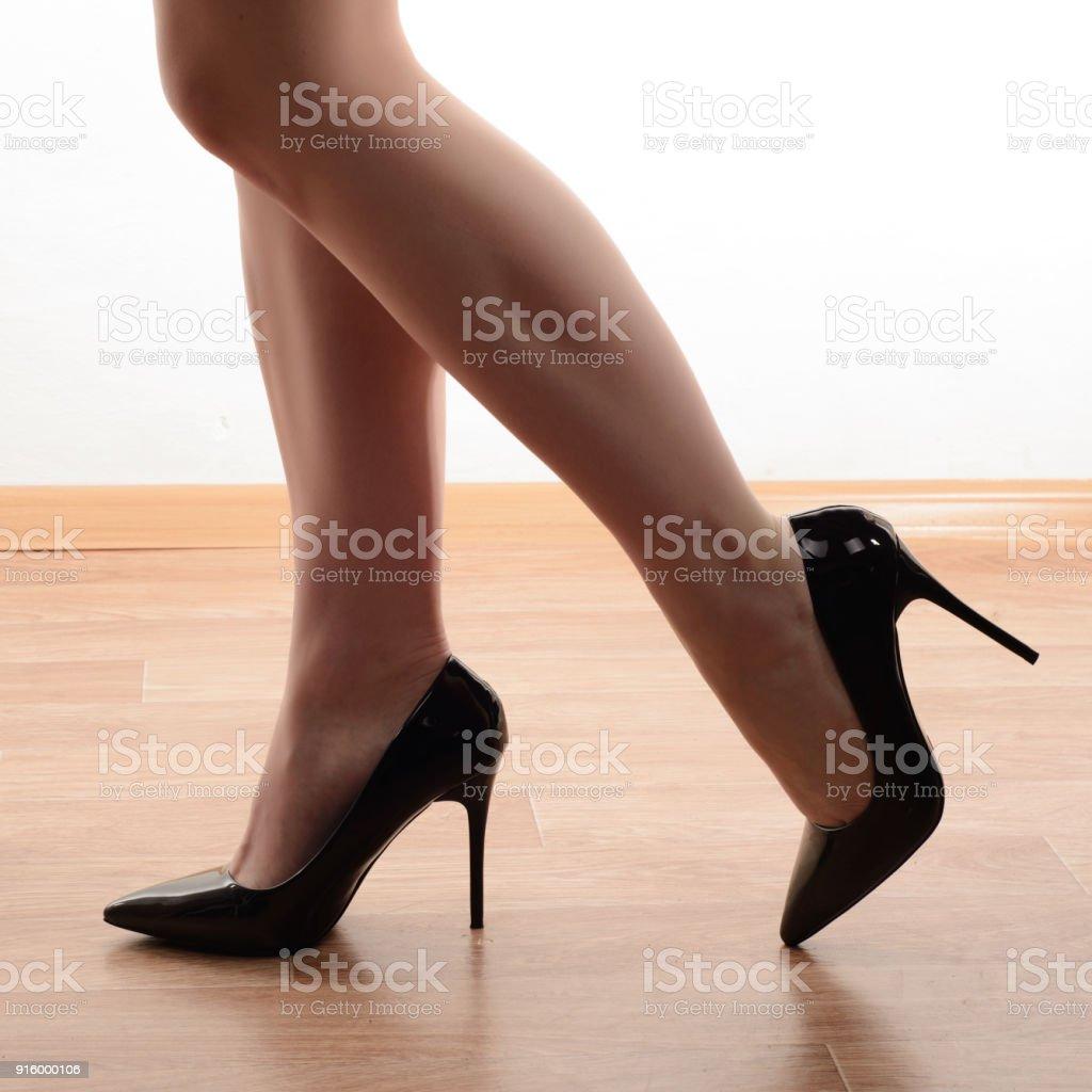 Close-up de Jovem mulher pernas em preto sapatos de salto alto - foto de acervo