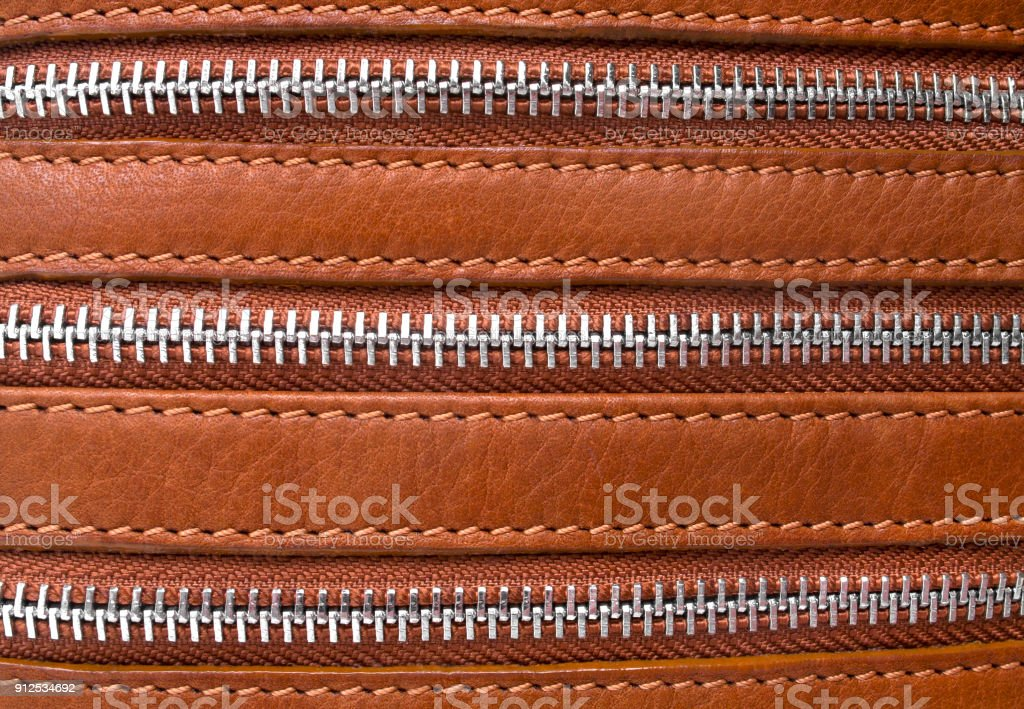 Closeup of zipper on the brown leather, can use as background stock photo