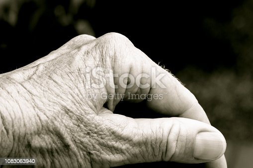 Closeup side view of old woman's hand, black and white, background with copy space, full frame horizontal composition