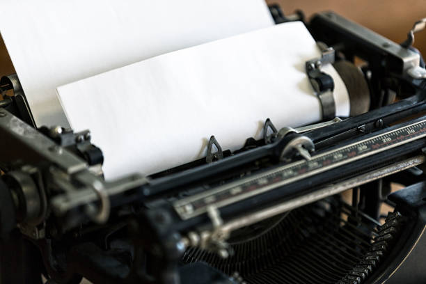 Close-Up Old-Fashioned Manual Typewriter with Blank Paper in Roller stock photo
