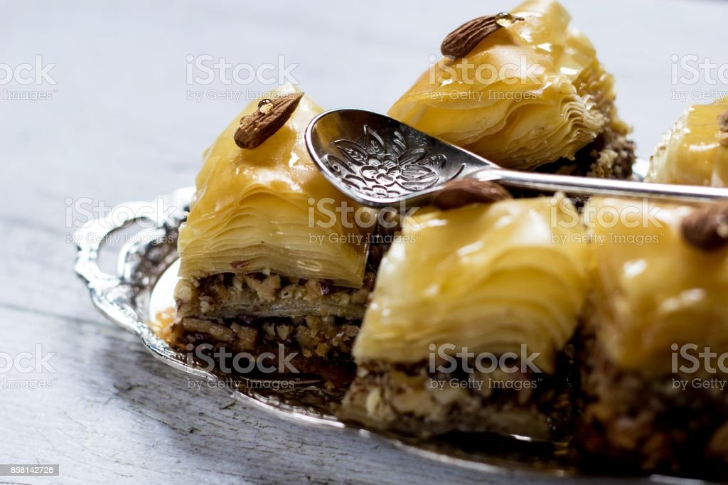 Closeup on a baklava on a silver tray with an ornamental spoon o a white wooden background stock photo