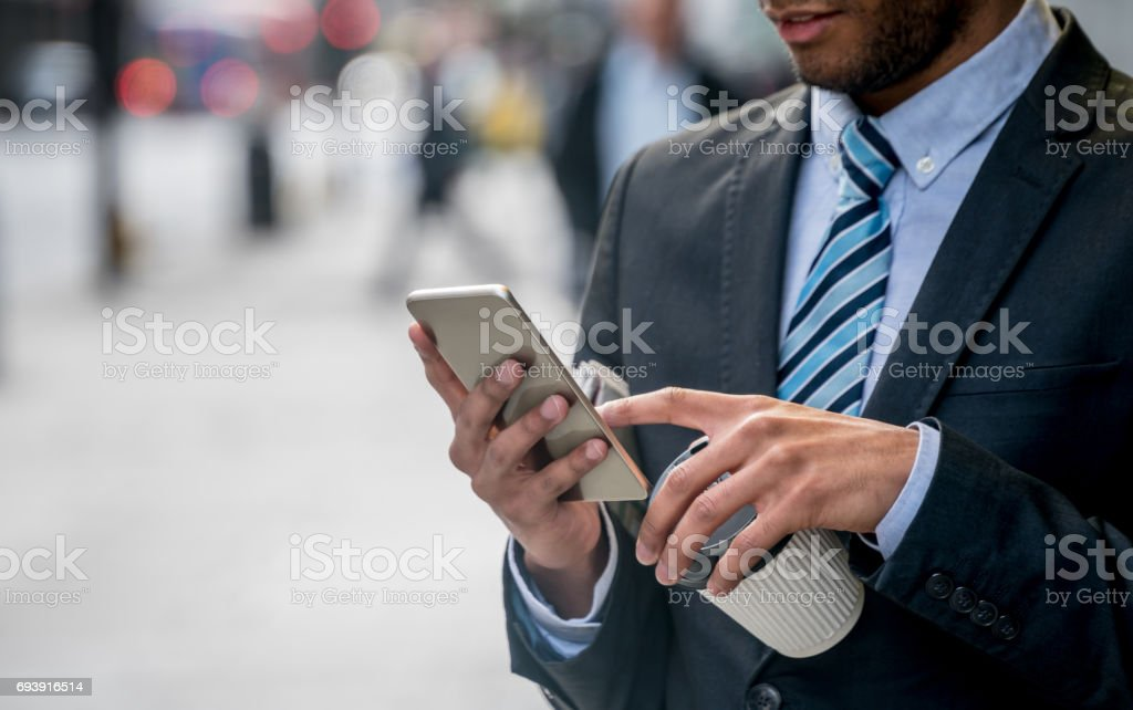 Close-up on a business man texting on his phone on the street stock photo