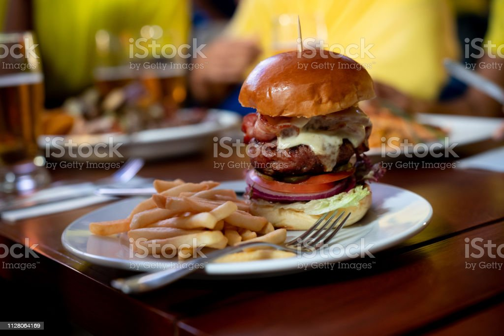 Close-up on a cheese burger served at a sports bar - lifestyle...