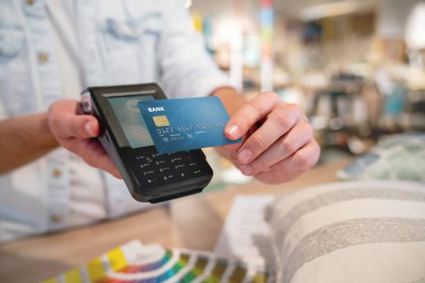 Primer plano de un pago sin contacto en una tienda de muebles - foto de stock