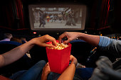 Close-up on a couple at the movies eating popcorn - entertainment concepts. **IMAGE ON SCREEN IS OURS**