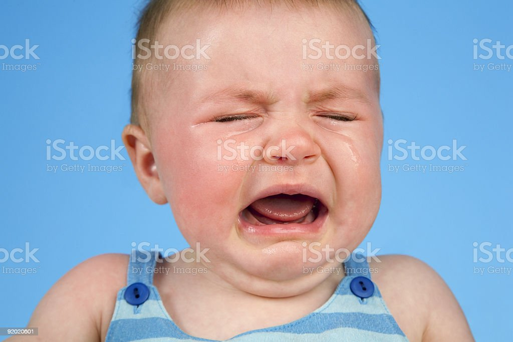 Close-up on a crying baby boy over a blue background royalty-free stock photo