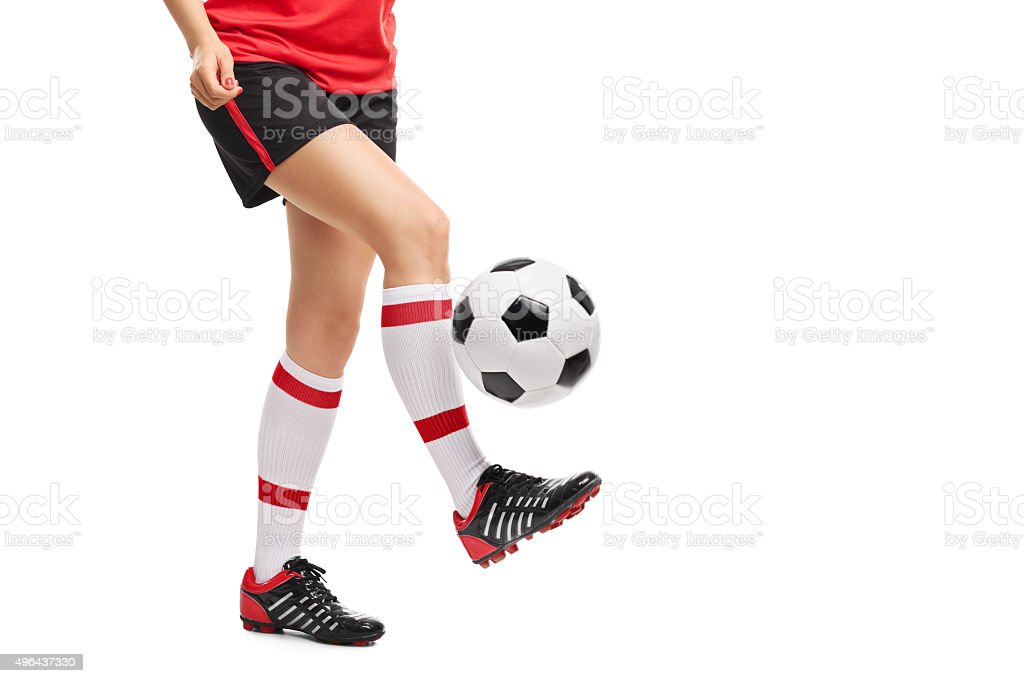 Close-up on a female football player jugling a ball stock photo