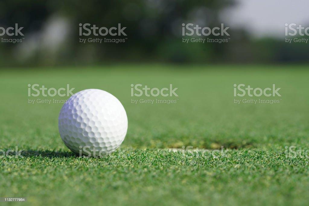 Close-up on a golf ball on a green grass near the hole