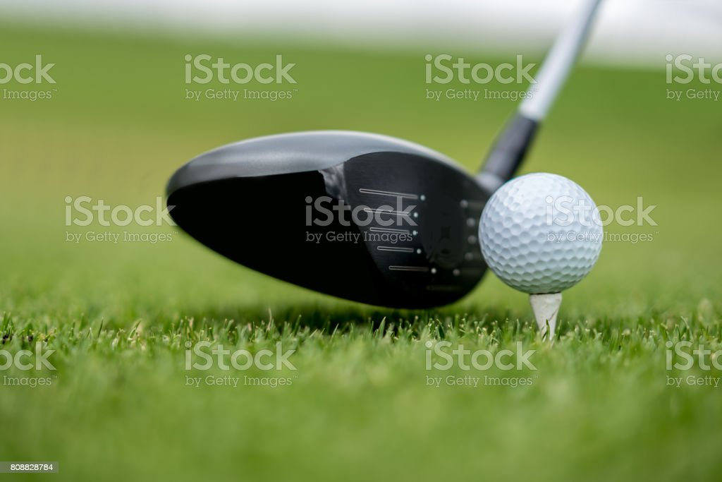 Close-up on a golf club hitting the ball stock photo