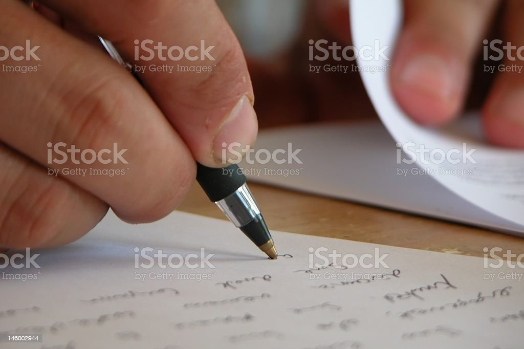 Close-up on a hand writing a letter with a ball pen royalty-free stock photo