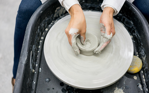 Close-up on a person doing pottery with clay