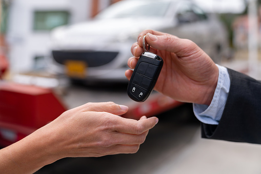 Close-up on a salesman delivering a car while handling the keys - car ownership concepts