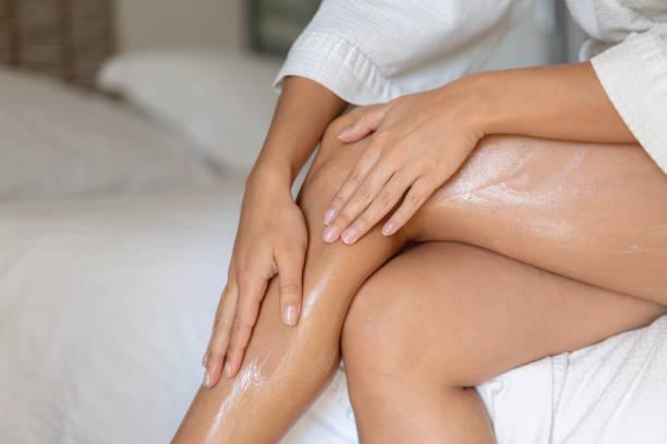 primo-up su una donna che applica la crema sulle gambe - il corpo umano foto e immagini stock