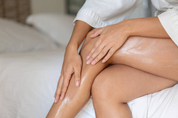 close-up on a woman applying cream on her legs - corpo foto e immagini stock