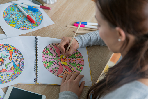 Close-up on a happy young woman coloring mandalas at home - wellness concepts