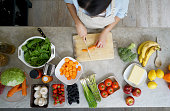 Close-up on a woman cooking at home chopping vegetables and making a salad