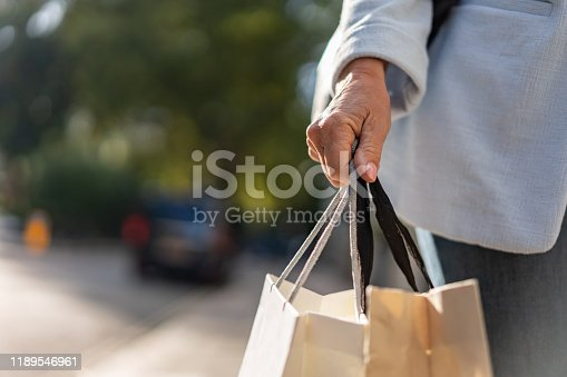 Close-up on a woman holding shopping bags on the street