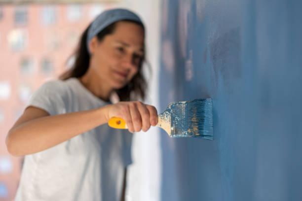 Nahaufnahme auf eine Frau, die ihr Haus malt – Foto