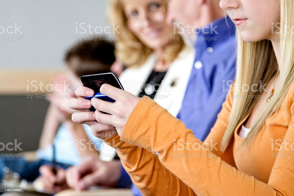 Close-up on a young girl texting on a slide mobile phone royalty-free stock photo