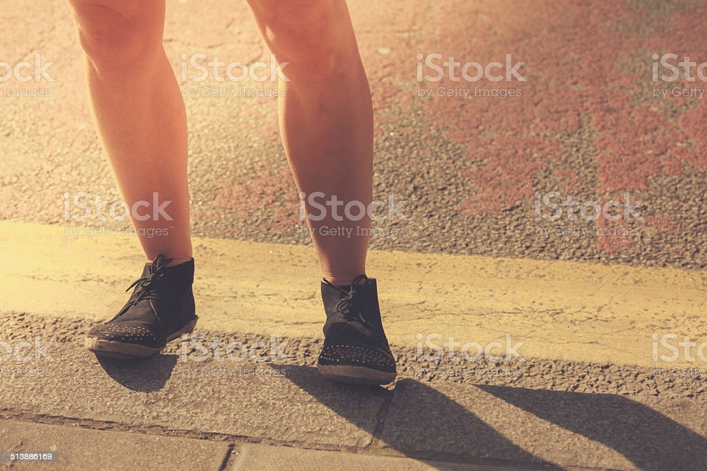 Closeup on a young woman's legs in the street stock photo