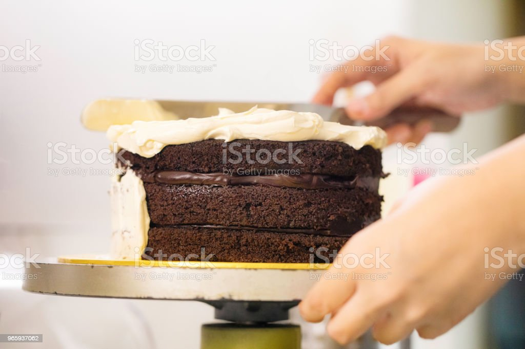 Close-up on baker's hands covering layered Chocolate cake with buttercream icing - Royalty-free Adult Stock Photo
