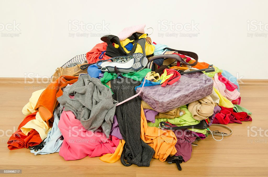 Closeup on big pile of clothes thrown on the ground. stock photo