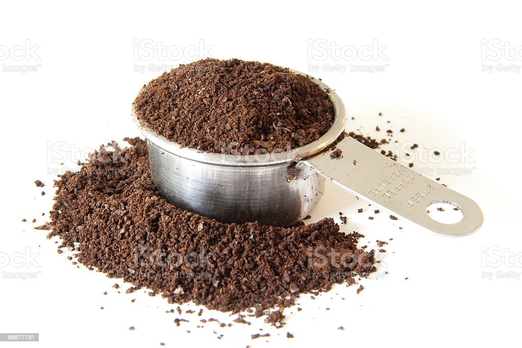 Closeup on black ground coffee in a measuring cup stock photo